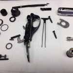 Completely disassembled trigger assembly for a Remington 870 shotgun